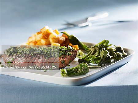 Steak coated in herbs with Pimientos de Padron Stock Photo - Premium Royalty-Free, Image code: 659-03534025