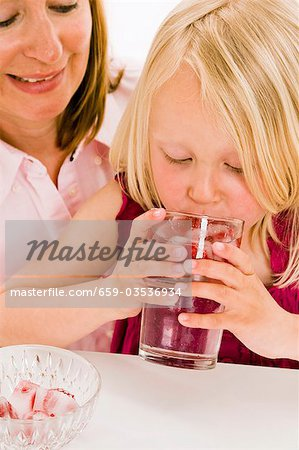 Girl drinking water with raspberry ice cubes Stock Photo - Premium Royalty-Free, Image code: 659-03536934