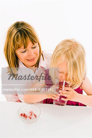 Girl drinking water with raspberry ice cubes Stock Photo - Premium Royalty-Free, Image code: 659-03536935