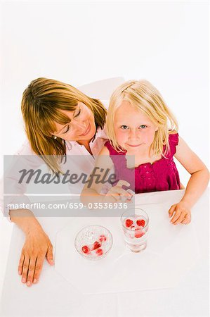 Mother and daughter, daughter holding a raspberry ice cube Stock Photo - Premium Royalty-Free, Image code: 659-03536936