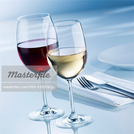 Glass of white wine and glass of red wine beside place-setting Stock Photo - Premium Royalty-Free, Image code: 659-03537621