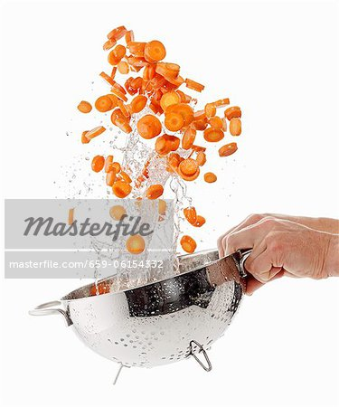 Sliced carrots being washed Stock Photo - Premium Royalty-Free, Image code: 659-06154332