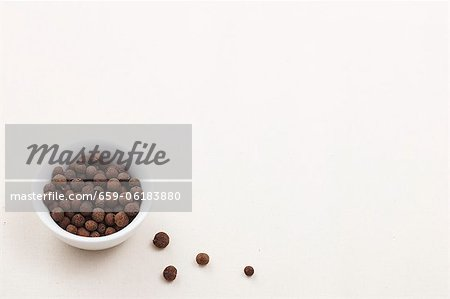 Allspice berries in a bowl and next to it Stock Photo - Premium Royalty-Free, Image code: 659-06183880