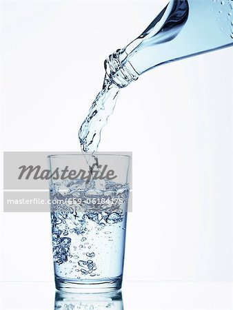 Pouring water from a bottle into a glass Stock Photo - Premium Royalty-Free, Image code: 659-06184175