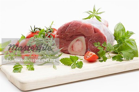 Veal knuckle with herbs and tomatoes on a chopping board