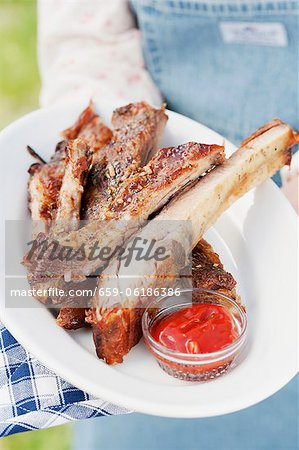 A person holding a plate of grilled spare ribs and barbecue sauce Stock Photo - Premium Royalty-Free, Image code: 659-06186386