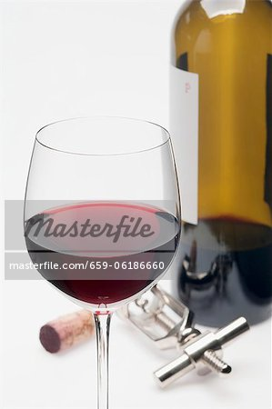 A glass of red wine, cork, corkscrew and bottle of red wine Stock Photo - Premium Royalty-Free, Image code: 659-06186660