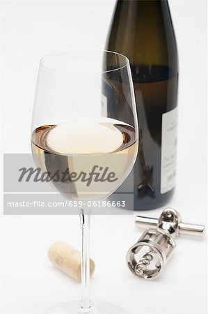 A glass of white wine, cork, corkscrew and bottle of white wine Stock Photo - Premium Royalty-Free, Image code: 659-06186663