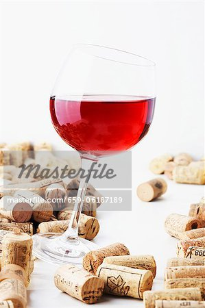 A glass of red wine with corks Stock Photo - Premium Royalty-Free, Image code: 659-06187189