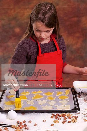 A girl brushing biscuits on a baking tray with egg yolk Stock Photo - Premium Royalty-Free, Image code: 659-06188557