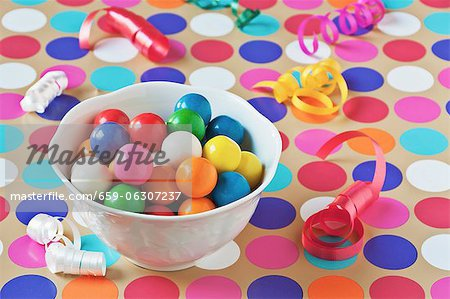 A Bowl of Colorful Gumballs on a Polk-a-Dot Table Cloth with Scattered Party Ribbons Stock Photo - Premium Royalty-Free, Image code: 659-06307237