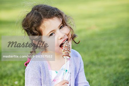 A little girl eating marshmallows Stock Photo - Premium Royalty-Free, Image code: 659-06307502