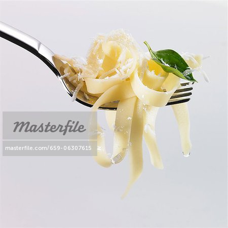 Tagliatelle, oil, basil and grated Parmesan on a fork Stock Photo - Premium Royalty-Free, Image code: 659-06307615