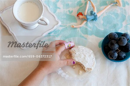 Little Girl's Hand Grabbing Cookie; Glass of Milk; Toy Stock Photo - Premium Royalty-Free, Image code: 659-06372317