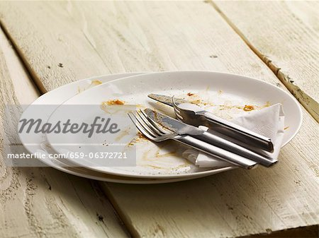 A dirty plate with cutlery and a paper napkin Stock Photo - Premium Royalty-Free, Image code: 659-06372721