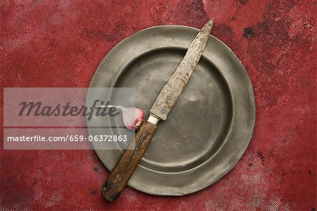 A knife and a garlic clove on a tin plate Stock Photo - Premium Royalty-Free, Image code: 659-06372863