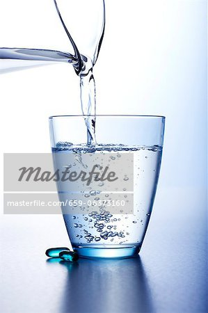Pouring Water Into a Glass From a Pitcher Stock Photo - Premium Royalty-Free, Image code: 659-06373160