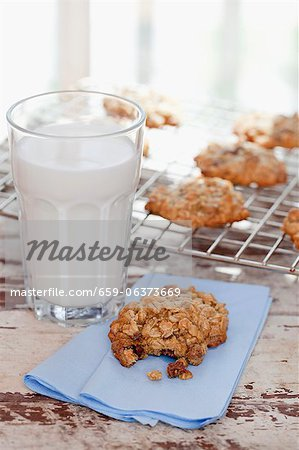 Homemade Oatmeal Cookies with a Glass of Milk; One Cookie with Bite Taken Out; Cookies on Cooling Rack Stock Photo - Premium Royalty-Free, Image code: 659-06373669