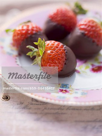 Chocolate strawberries on a pink, floral-patterned plate Stock Photo - Premium Royalty-Free, Image code: 659-06495417