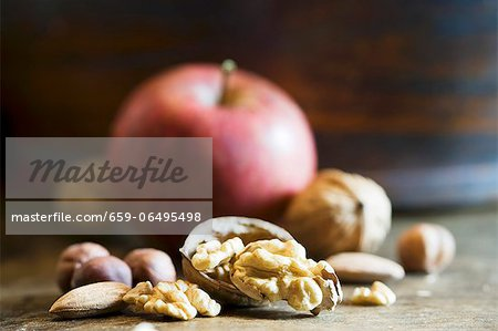 An arrangement of walnuts, nuts and an apple Stock Photo - Premium Royalty-Free, Image code: 659-06495498