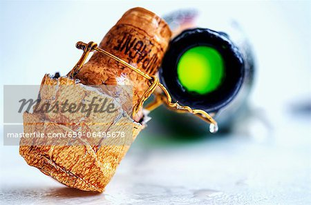 A champagne cork and an open bottle of champagne Stock Photo - Premium Royalty-Free, Image code: 659-06495678