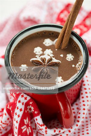 A cup of hot chocolate with star anise, a cinnamon stick and snow flakes Stock Photo - Premium Royalty-Free, Image code: 659-06671259