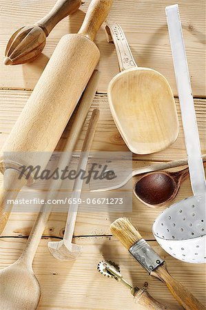 Kitchen utensils on a pale wooden surface Stock Photo - Premium Royalty-Free, Image code: 659-06671273