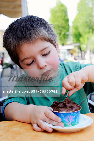 A little boy eating chocolate ice cream in an ice cream cafe Stock Photo - Premium Royalty-Free, Image code: 659-06900781