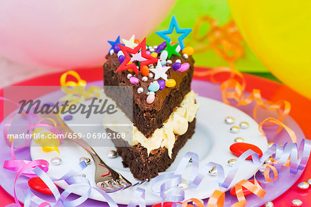 A piece of chocolate cake with colorful sprinkles and candy decorations for a party Stock Photo - Premium Royalty-Free, Image code: 659-06902168
