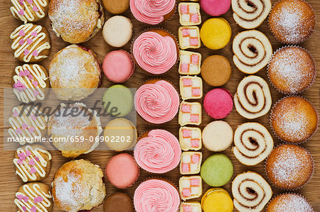 Rows of cupcakes, scones, macarons, Swiss rolls and pieces of mini-Battenburg cake Stock Photo - Premium Royalty-Free, Image code: 659-06902202