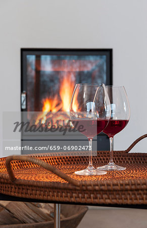 Two glasses of red wine on a table in front of a fireplace Stock Photo - Premium Royalty-Free, Image code: 659-06902473