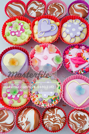 overview o of coloured cup cakes in red and pink plastic cake covers decorated with hearts, lips and sweets Stock Photo - Premium Royalty-Free, Image code: 659-06903182
