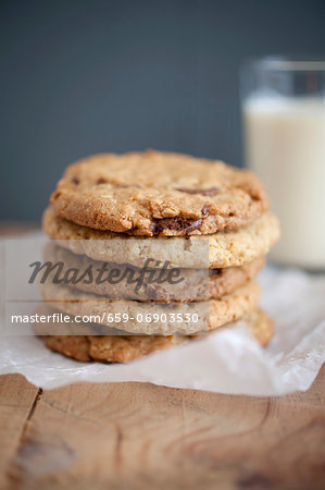 Chocolate chip, peanut butter and oatmeal cookies stacked on baking parchment wih a glass of milk in the background. Stock Photo - Premium Royalty-Free, Image code: 659-06903530