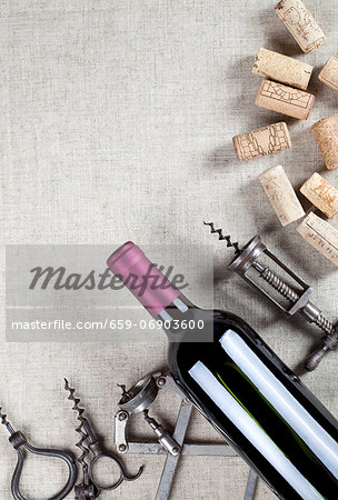 A bottle of red wine, old corkscrews and wine corks Stock Photo - Premium Royalty-Free, Image code: 659-06903600