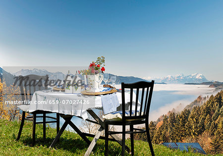 A table laid in the country house style, on an alpine meadow with a view over the Alps Stock Photo - Premium Royalty-Free, Image code: 659-07027426