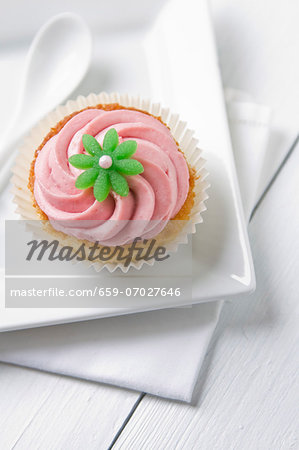 A cupcake topped with pink icing and a green flower Stock Photo - Premium Royalty-Free, Image code: 659-07027646