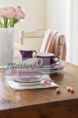 Stacked plates and coffee cups next to pink ranunculus flowers in a vase Stock Photo - Premium Royalty-Free, Image code: 659-07027670
