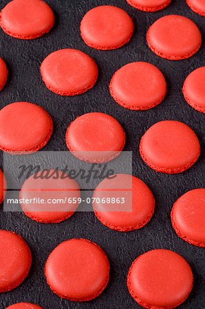 Freshly baked red macaroon halves on a slate surface Stock Photo - Premium Royalty-Free, Image code: 659-07068863