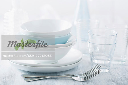 Stacked dinner bowls and plated, drinking glasses and forks Stock Photo - Premium Royalty-Free, Image code: 659-07069253