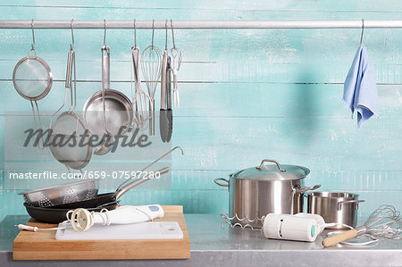 Assorted kitchen utensils on a stainless steel unit and hanging on a metal rod Stock Photo - Premium Royalty-Free, Image code: 659-07597280