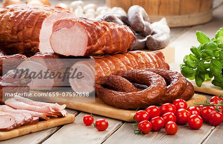 Assorted sausages and ham, cherry tomatoes, basil and garlic Stock Photo - Premium Royalty-Free, Image code: 659-07597658