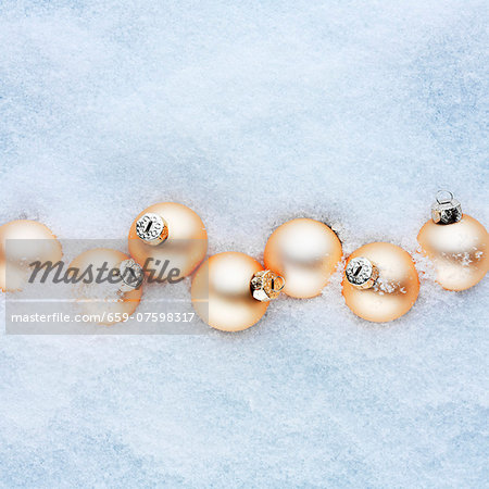 Apricot-coloured Christmas baubles in the snow Stock Photo - Premium Royalty-Free, Image code: 659-07598317