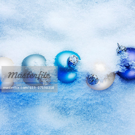 Blue and apricot-coloured Christmas baubles hidden in the snow Stock Photo - Premium Royalty-Free, Image code: 659-07598318