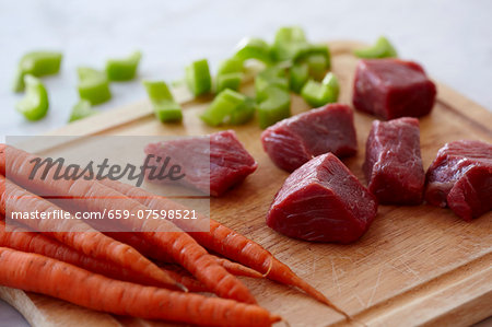 Chunks of Raw Beef, Raw Carrots and Chopped Celery on a Wooden Cutting Board Stock Photo - Premium Royalty-Free, Image code: 659-07598521
