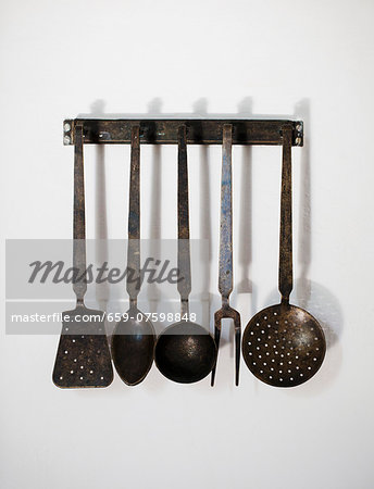 Old kitchen utensils hanging on the wall Stock Photo - Premium Royalty-Free, Image code: 659-07598848
