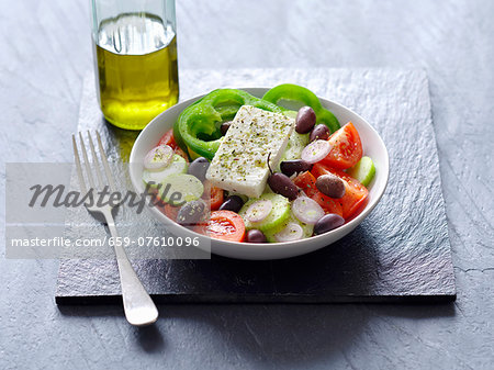 A Greek salad next to a bottle of olive oil Stock Photo - Premium Royalty-Free, Image code: 659-07610096