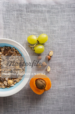A bowl of muesli next to grapes, nuts and an apricot Stock Photo - Premium Royalty-Free, Image code: 659-07610362