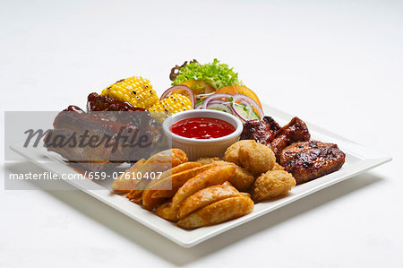 Spare ribs and chicken wings with potato wedges, corn on the cob and ketchup Stock Photo - Premium Royalty-Free, Image code: 659-07610407