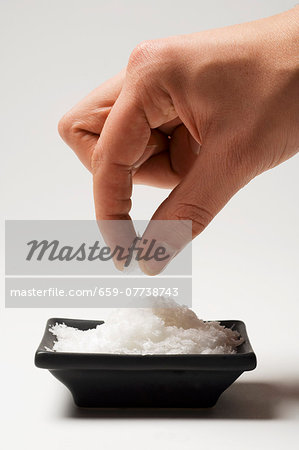 A hand taking a pinch of salt from a dish Stock Photo - Premium Royalty-Free, Image code: 659-07738743