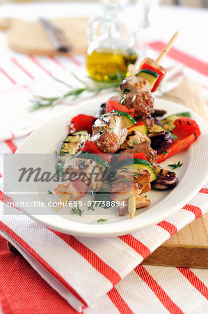 Barbecued kebabs with sausage, bacon and pancetta on grilled vegetables Stock Photo - Premium Royalty-Free, Image code: 659-07738894